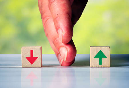 The hand separates two wooden blocki with red arrow down and green arrow up. Symbol for the difference between rise and fall in business