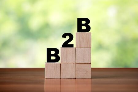 Wooden cube block shapes as step stairs with B2B Business to Business word. Business concept, success and growth finance. 免版税图像