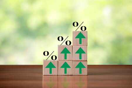 Wooden cube block shapes as step stairs with percent sign and green arrows pointing up. Business concept, success and growth finance.