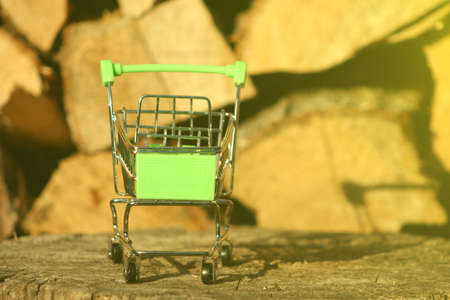 A mini shopping trolley on a table that shines on the sun symbolizing marketing and shopping as a concept of business.