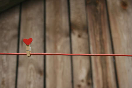 Clothes peg with a red heart on a string against the background of old boards. Archivio Fotografico