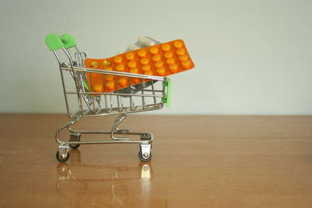 Shopping trolley with pills and tablets. Variety of pills and drugs in mini basket. Pharmacy Shopping Concept.