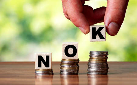 NOK currency word symbol - business concept. Hands put wooden block on stacked increasing coin.