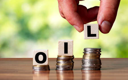OIL word symbol - business concept. Hands put wooden block on stacked increasing coin.