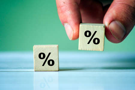 Business man Hand putting wood cube block with percentage symbol icon. Interest rate, financial, ranking and mortgage rates.
