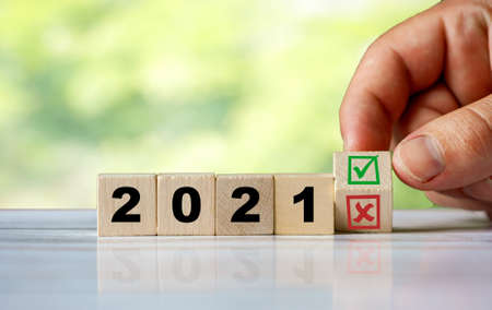 The hand turns the wooden cube and change the word 2021 with green positive tick check box and red reject X check box. new year welcomed. Start 2021.