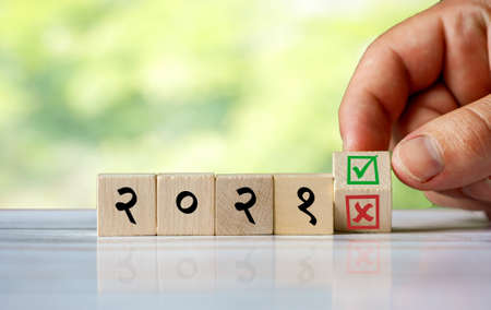 The hand turns the wooden cube and changes the hindi word (english = 2021) with green positive tick check box and red reject X check box. Indian word as start 2021 new year concept