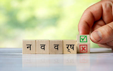 The hand turns the wooden cube and changes the hindi word (english = new year) with green positive tick check box and red reject X check box. Indian word as new year concept