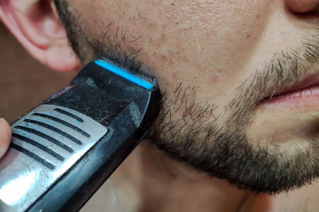 Man shaving his beard off with an electric shaver. Handsome young bearded man trimming his beard with a trimmer