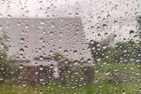 Water drop of rain on window glass burred garden background.