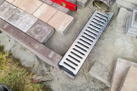 iron drainage net. Drain for water after rain on the sidewalk. Installation of paving slabs and drainage systems