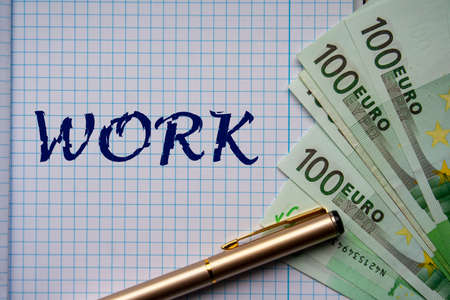 The WORK word on notebook page and euro banknotes. Financial or business concept. 版權商用圖片