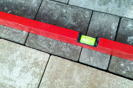 Laying paving stones. Measuring the slope with a spirit level. Laying paving stones on sand. A spirit level for measuring in construction concept 版權商用圖片