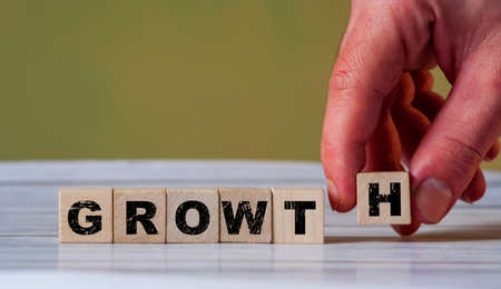 The hand put wooden cube block and creates word GROWTH. Increase business concept