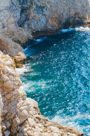rocky coastline: Rocky coastline with blue water and waves
