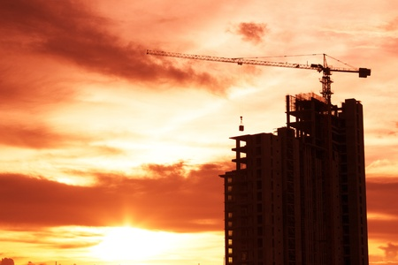 Building crane and building under construction against Sunset photo