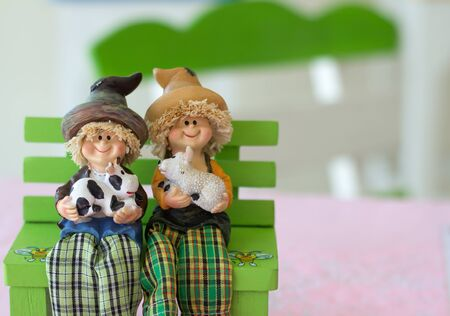 degrading: dolls sitting on an armchair. Stock Photo