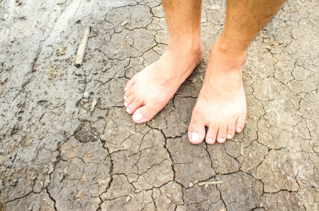barrenness: Foot on dry soil texture background Stock Photo