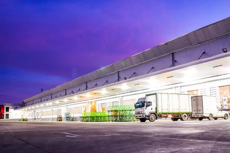 Witte vrachtwagens geparkeerd op een parkeerplaats plaatsen in het magazijn