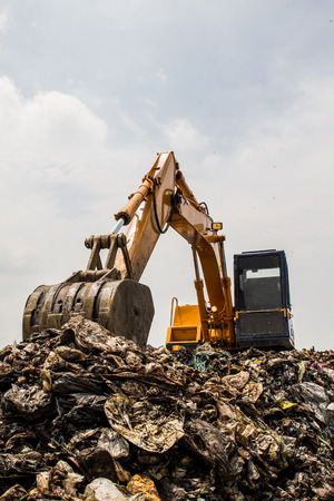 scarp: mountain of garbage with working backhoe Stock Photo