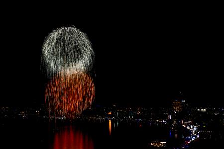 PATTAYA - NOVEMBER 28: The colorful firework and skyscrapers at Pattaya bay during Pattaya International Fireworks Festival 2014 on November 28,2014 in Pattaya,Thailand.