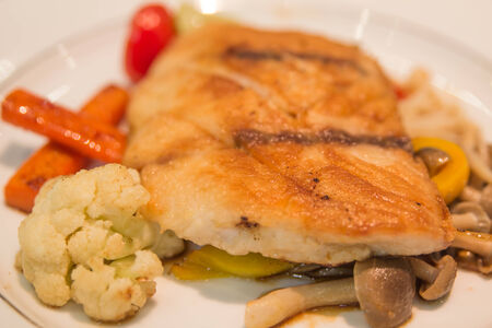 Snapper steak with sauce and boiled vegetables photo