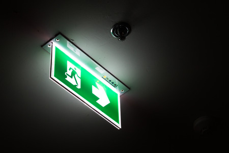 Emergency exit sign above a black doorway at night.