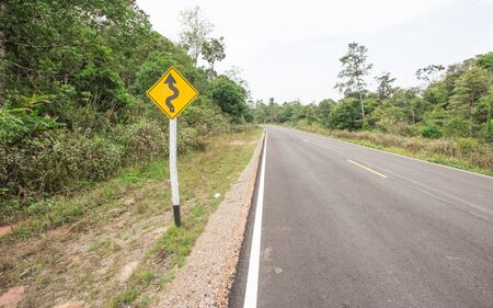 rural road: Curvy road sign to the mountain in rural area