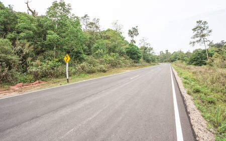 rural area: Curvy road sign to the mountain in rural area