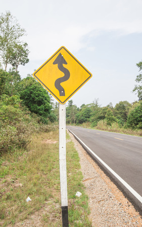 Curvy road sign to the mountain in rural area photo