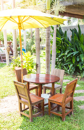 wooden dining table set in lush garden setting and light sun photo