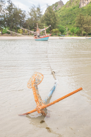 threw: Fishing boat threw the anchor on the shore. Stock Photo