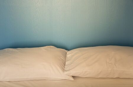 unmade: An unmade bed with white linens background blue wood Stock Photo