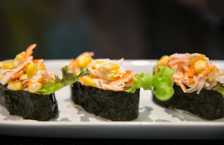 soysauce: Three pieces of sushi on a plate