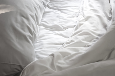 messy: Messy white bed and the light shines, in the morning Stock Photo