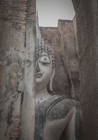 colonade: ancient seated buddha staue in the temple ruins of sukhothai in thailand.