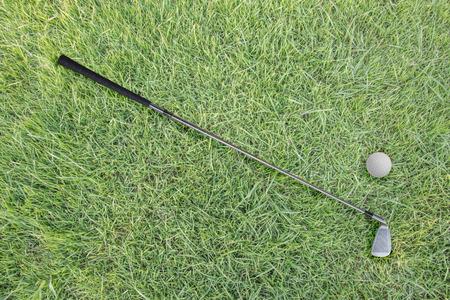caddie: Golf club and ball on green grass