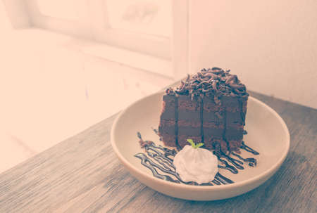 chocolaty: Chocolate cake with chocolate buttercream frosting and ganache and optical window, cut out, selective focus. Vintage filter.