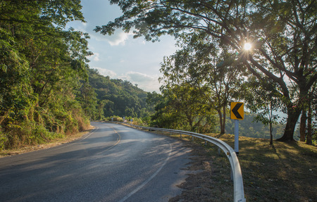 Asphalt road sharp curve along with tropical forest zigzag ahead. Stock Photo