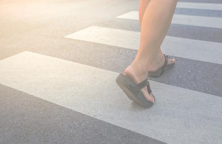 A woman crossing a crosswalk Stock Photo