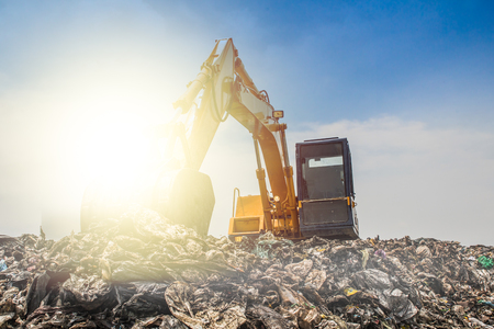 mountain of garbage with working backhoe Stock Photo