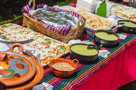 Table of Mexican Buffet with tacos enchiladas chalupas and tamales on a sunny day Banque d'images
