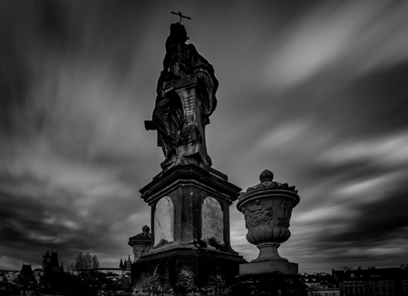 A black and white photograph of a statue captured by a long exposure with a dramatic sky