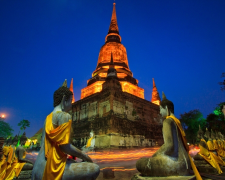 Old temple walking with lighted candles in hand around a temple candle light trail of Buddhism Ceremony at temple ruin on Magha Puja Day thailand  photo