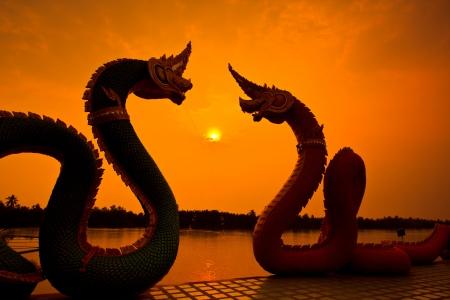 naga china: Silhouettes dragon and Naga statue protecting Thai temple