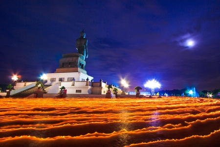 Buddha statue candle lit in lent day thailand and Walk with lighted candles in hand around a temple photo
