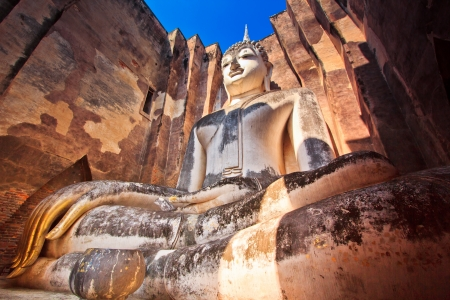 unesco world cultural heritage: Giant statue of a seated Buddha with tapered fingers covered with gold leaves in Sukhothai Historical Park - Thailand