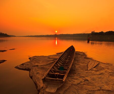 Silhouettes landscape view sunset and old wooden boats in mekong river ubon ratchathani province thailand  photo