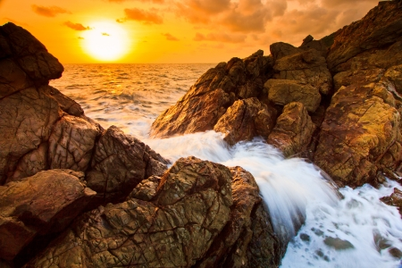 Landscape sunset sea waves line impact rock on the beach  Stock Photo