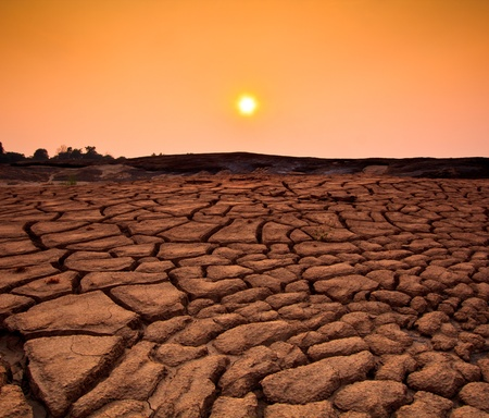 Sunset over cracked land and arid terrain  photo
